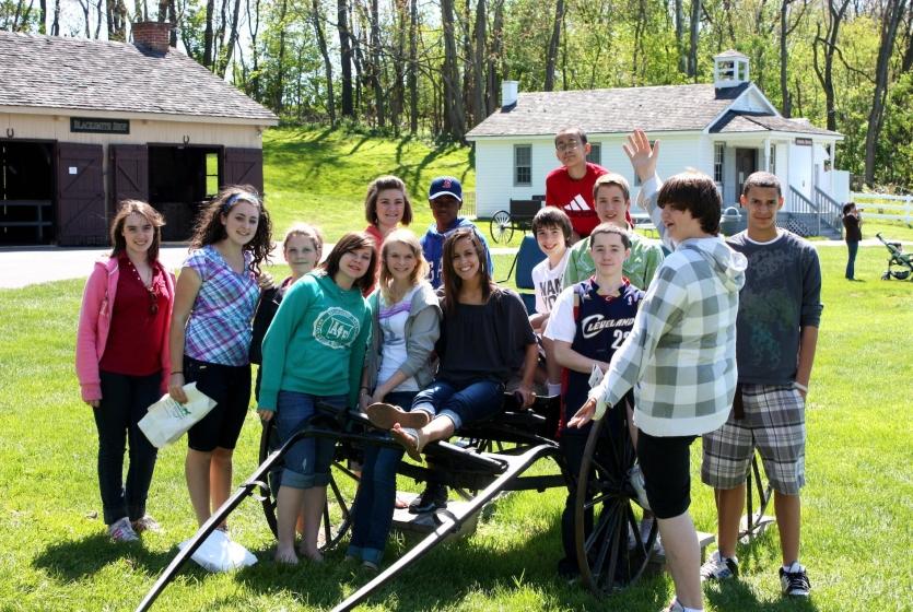 Group of kids around Amish wagon