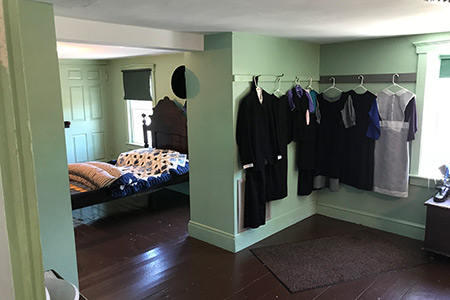 Clothing hanging in an Amish bedroom