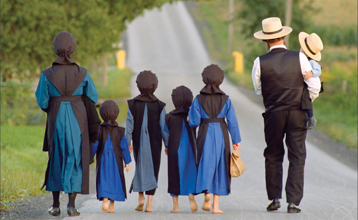An Amish family walking on a country road