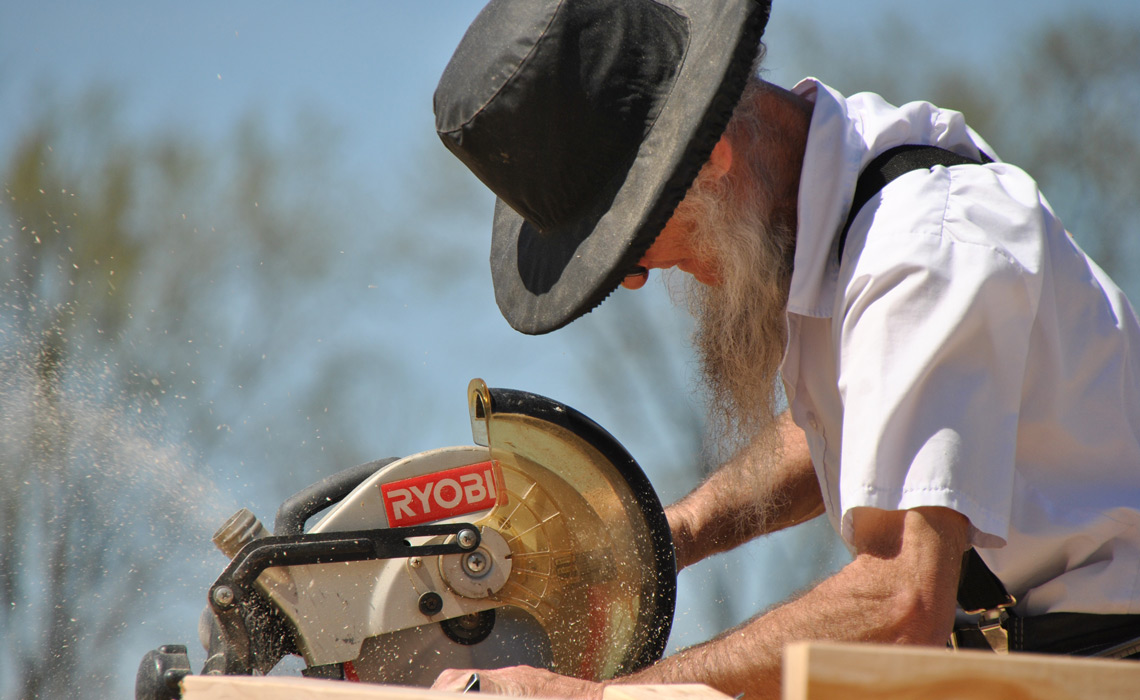 Amish man operating an electric mitre saw